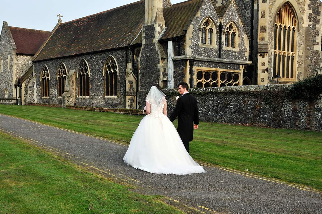 Newlyweds walking down the path together at Surrey wedding venue Carew Manor after getting married next door at St Mary's Church Beddington