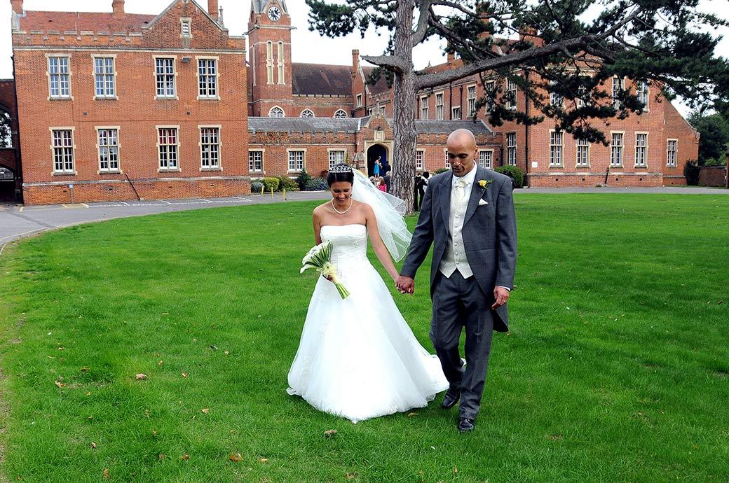 Bride and groom enjoy a private conversation as they stroll across the lawn from Carew Manor an old Surrey wedding venue in Beddington