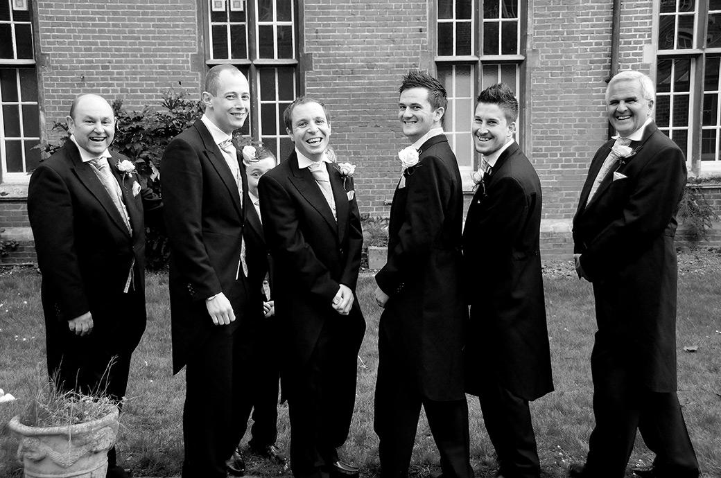 All smiles from the Groom and Groomsmen as they share a joke in the quadrangle at Carew Manor a fine wedding venue in Beddington Surrey