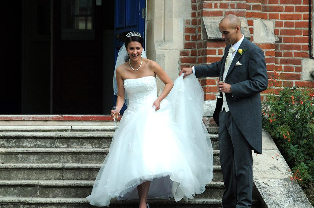 Groom helps smiling Bride down the steps of popular wedding venue Carew Manor in Beddington Surrey