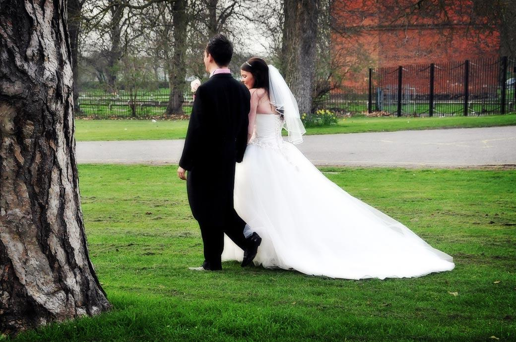 Bride and Groom walk hand in hand romantically across the front lawn of ancient Surrey wedding venue Carew Manor