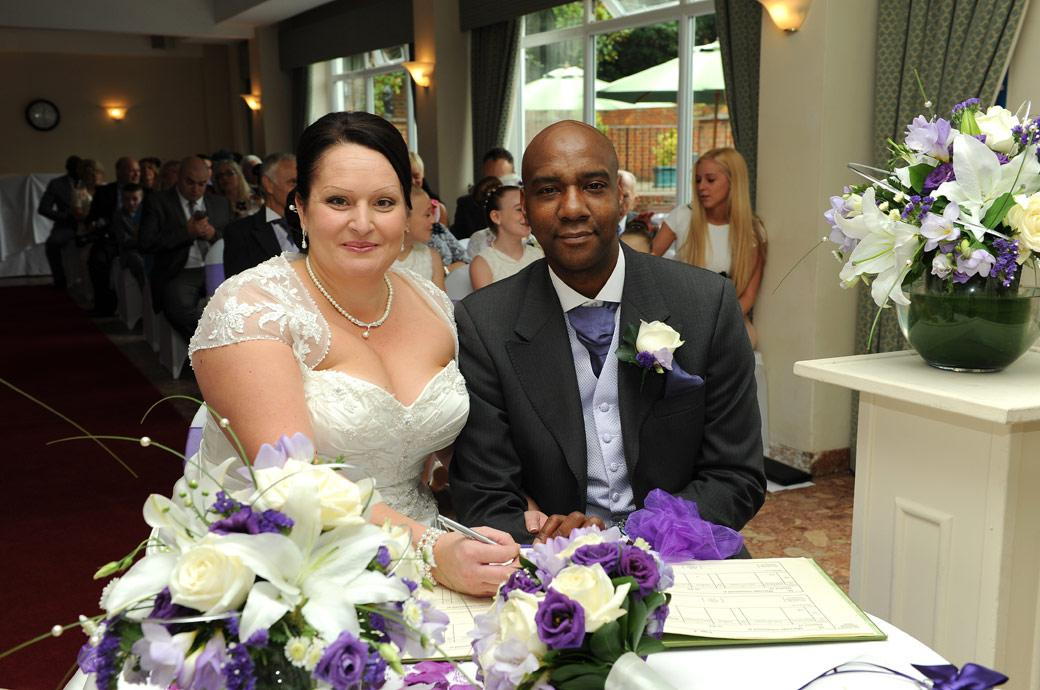 A happy Chalk Lane Hotel Bride and proud Groom pose for the Surrey Lane wedding photographer in this signing the marriage register wedding picture