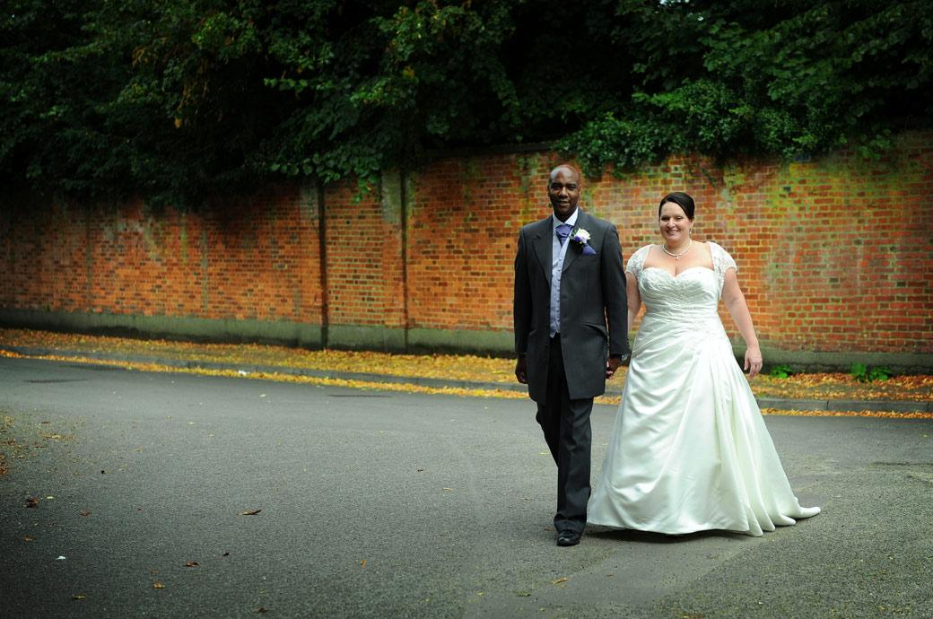 Relaxed and smiling newly-wed couple walk across the road in front of Surrey wedding venue Chalk Lane Hotel for a natural and  informal wedding picture