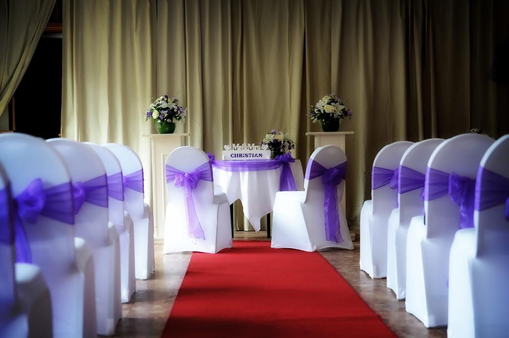 A Surrey wedding photograph of the Chalk Lane Hotel function room dressed with table flowers, red carpet and beautiful mauve chair sashes ready for the marriage ceremony