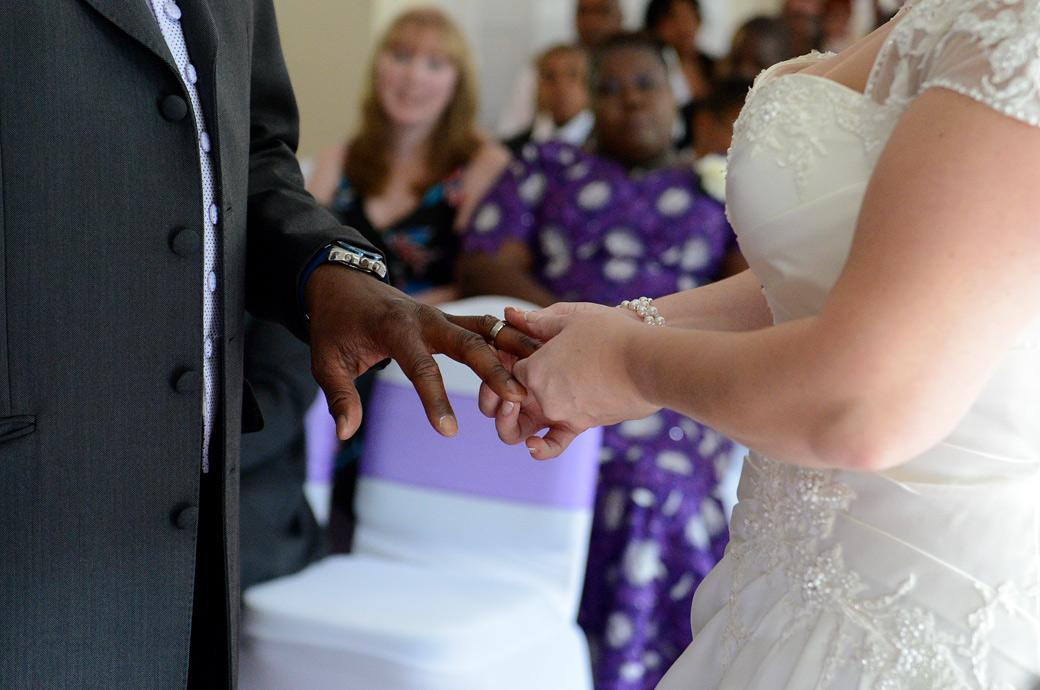 Bride holds the Groom's hand after placing the ring on his finger in this close up wedding photograph captured by a Surrey lane wedding photographer at the intimate Chalk Lane Hotel in Epsom