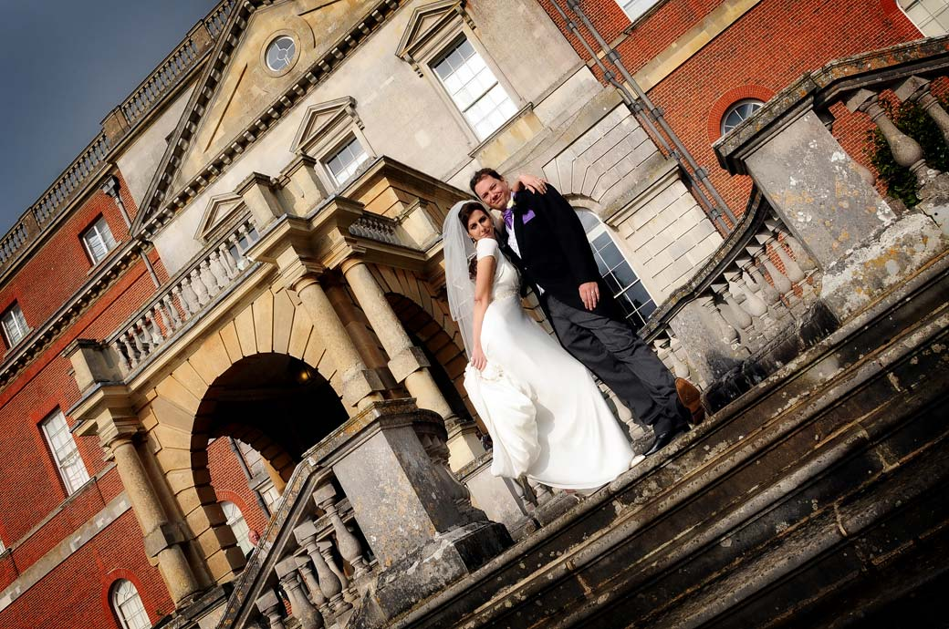 Bride grabs a pose with her new husband on the steps of the stunning Clandon Park in Guildford a photographers favourite Surrey wedding venue