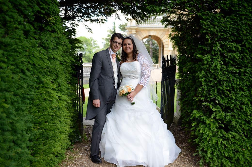 Relaxed Bride and Groom stand by the gate exiting from the parterre garden in this wedding photograph taken at the wonderful Surrey wedding venue Clandon Park