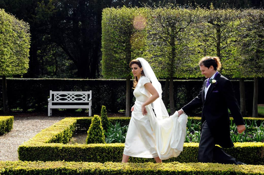 Happy Groom holds his Bride's wedding dress as they walk through the lovely Parterre garden wedding photograph taken at Clandon Park by Surrey Lane