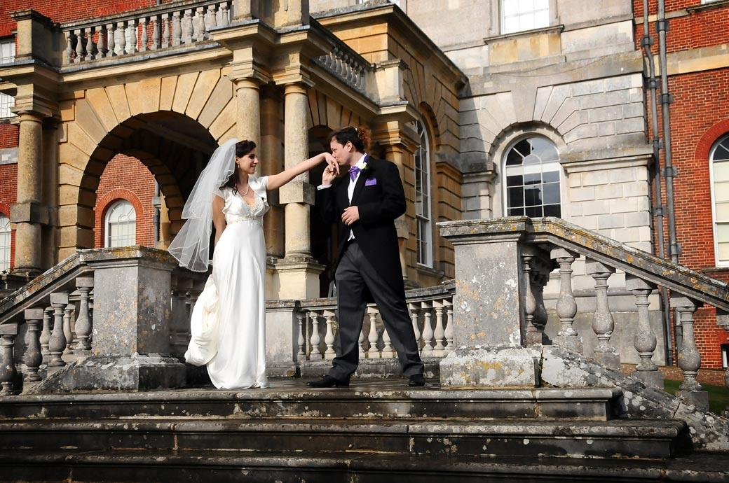 The Groom gallantly and theatrically kisses his Bride's hand on the sweeping main steps of the wonderful Surrey wedding venue Clandon Park in Guildford