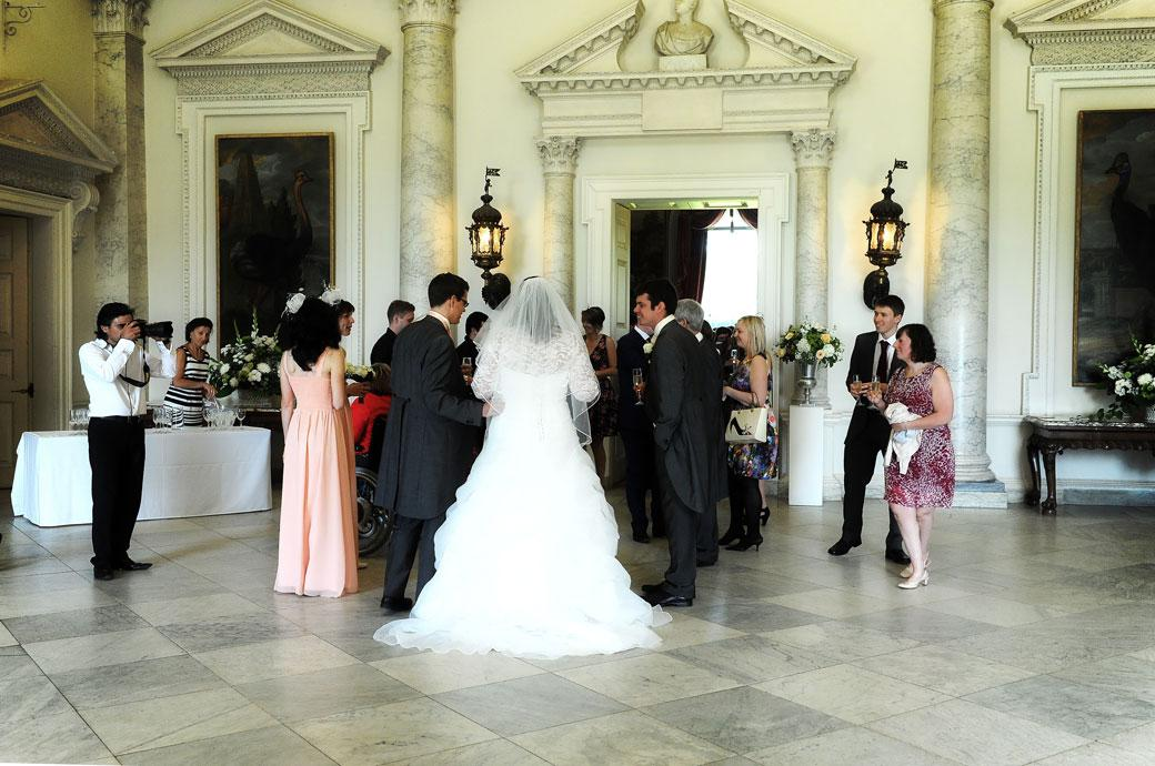 Bride and Groom in the wonderful marble Hall wait to greet their guests in this wedding photo taken as they leave the Tapestry Room for champagne and canapes at Clandon Park Surrey