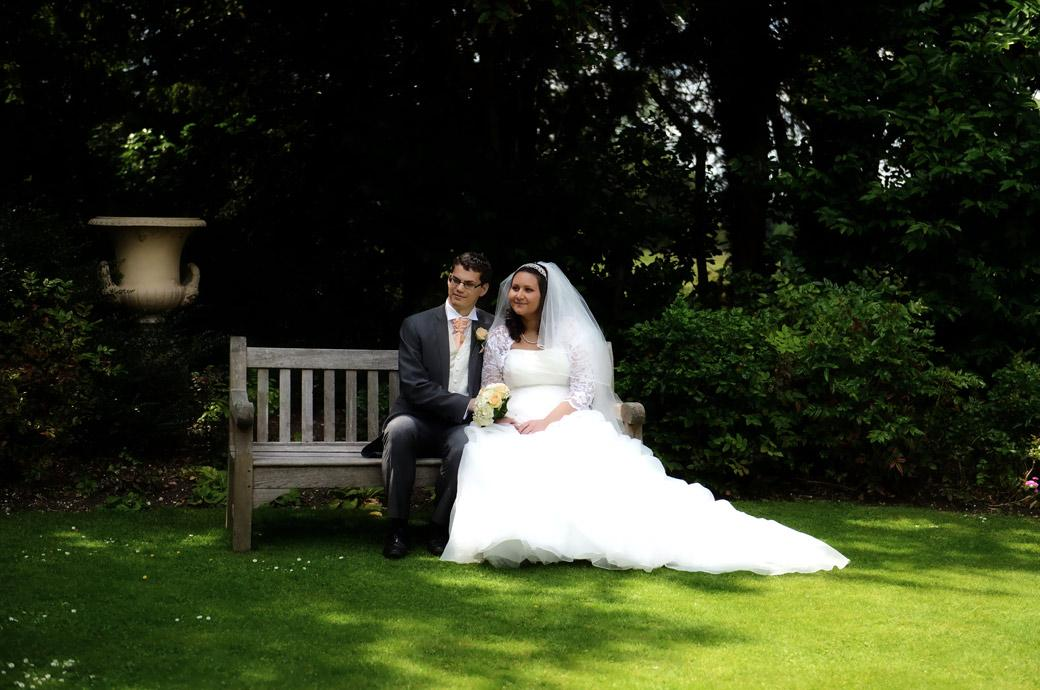 Bride and Groom relax on a bench in the serene and tranquil gardens at Clandon Park in this informal wedding photograph taken by a Surrey Lane wedding photographer