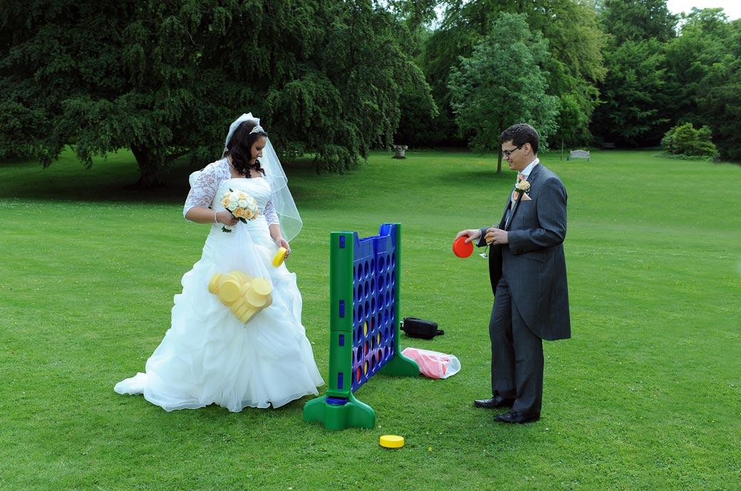 Fun and games for the Bride and Groom as they play giant Connect Four captured by Surrey Lane wedding photography on the lawn at the magnificent Clandon Park in Guildford