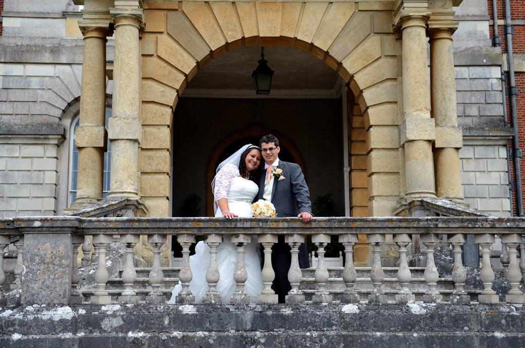 Bride rests on her husband's shoulder in this relaxed wedding photograph taken on the stone balustrade at Surrey wedding venue Clandon Park in Guildford