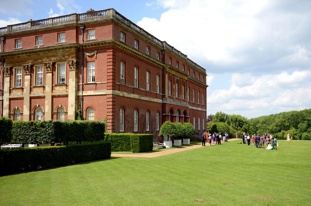 This wedding photograph show the guests playing games on the lawn in the distance and dwarfed by the massive Palladian Mansion Clandon Park in Guildford Surrey