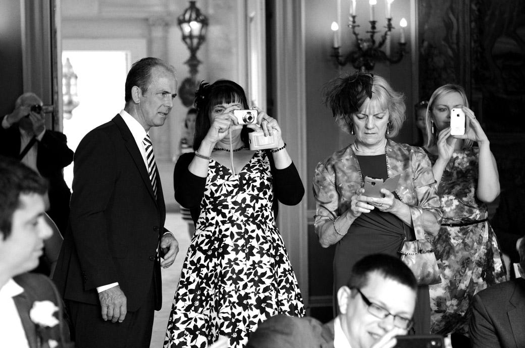 A close up wedding picture of guests taking photos of the happy couple after their marriage in the ornate Tapestry room at the stunning Surrey wedding venue Clandon Park