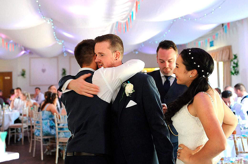 Wedding photo of the best man giving the Groom a lovely hug as the newlyweds come to inspect the wedding cake in the reception hall at Clock Barn Hall in Godalming Surrey