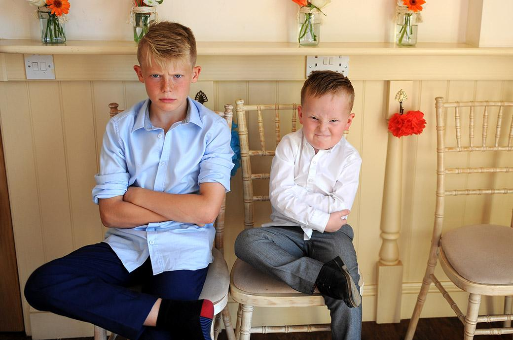A couple of boys put on their really mean serious faces for the Surrey Lane wedding photographer taken at the delightful and relaxing Clock Barn Hall Surrey wedding venue