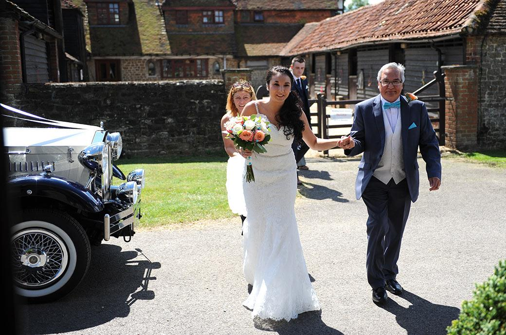 An excited and nervous Bride is walked from the wedding car by her father to the Bride's Room at the delightfully relaxed rural Surrey wedding venue Clock Barn Hall