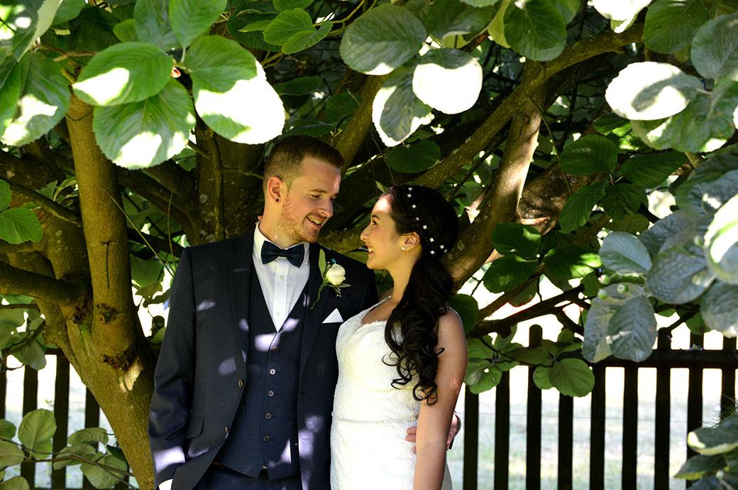 Lovely newlywed couple looking onto each other's eyes as they stand under a tree out of the bright summer sun at Clock Barn Hall Godalming a rural wedding venue in leafy Surrey