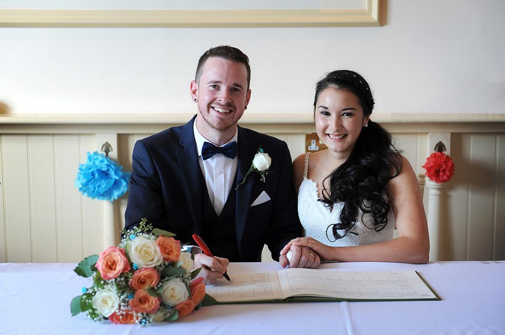 Delighted and happy Bride and Groom pose for the Surrey Lane wedding photographers at Clock Barn Hall as they sign their names in the marriage register