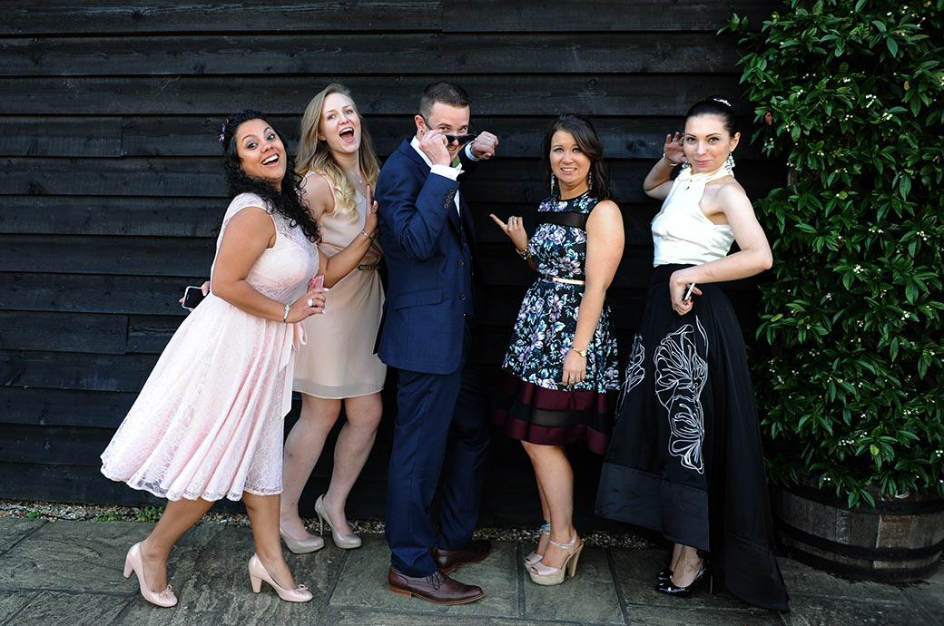Groom having fun as he poses with some of the ladies during the Clock Barn Hall reception in Godalming captured by Surrey Lane wedding photographers
