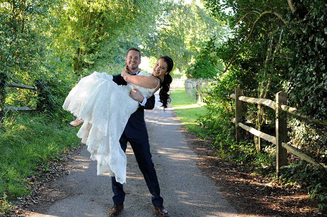 All smiles in this lovely Clock Barn Hall wedding photograph taken in rural Surrey as the smiling Groom lifts his beautiful smiling Bride and carries her down the country lane