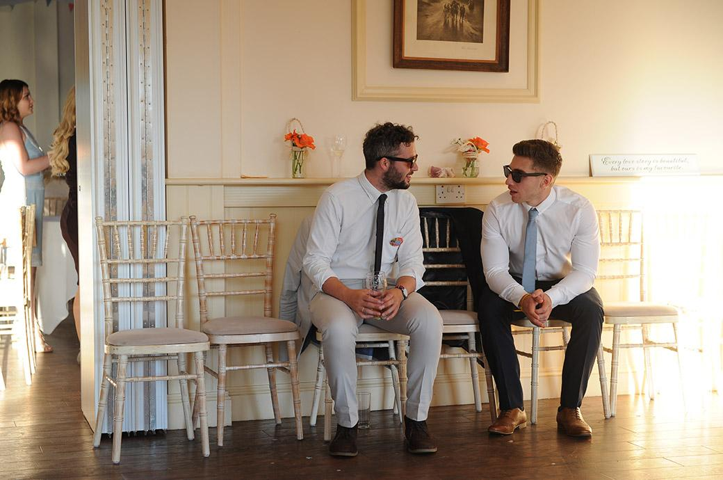 Male guests at the Surrey wedding venue Clock Barn Hall wearing sunglasses as they sit on chairs having a chat on the edge of the dance floor bathed in a natural evening sunlight
