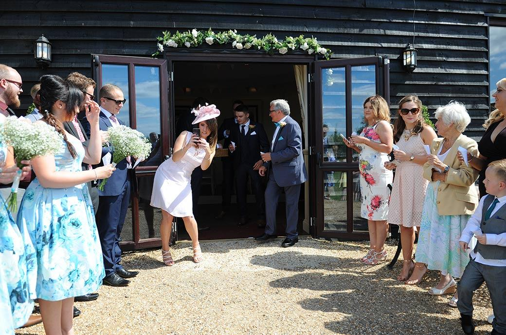 Guest getting her picture of the line of guests ready with their confetti  outside the ceremony room at the Clock Barn Hall wedding venue in Godalming Surrey