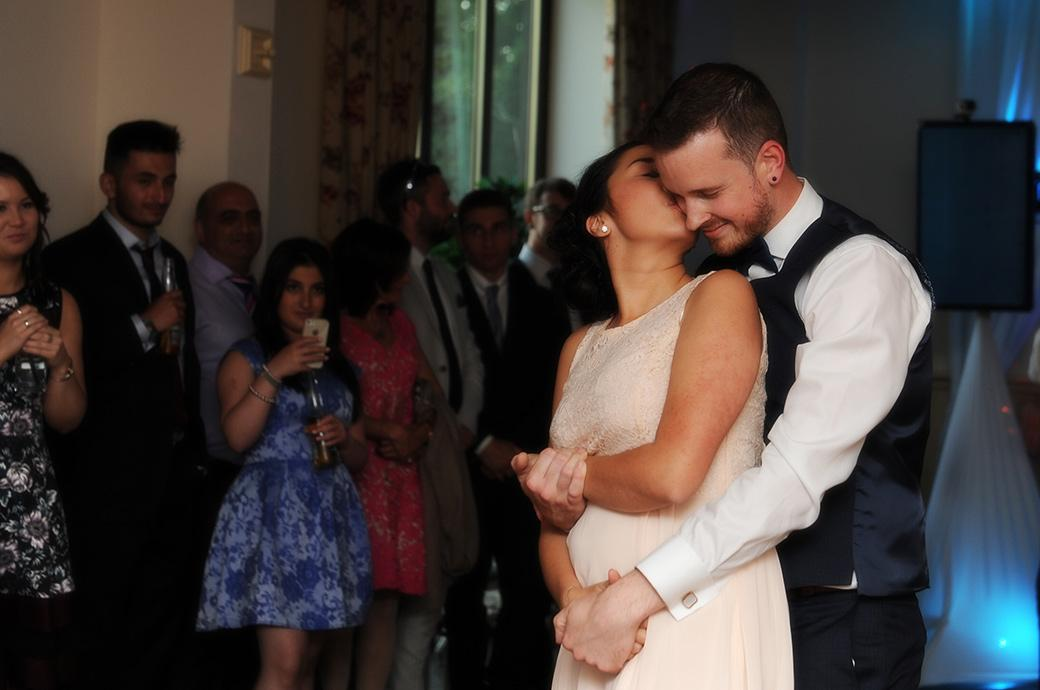 Romantic moment captured in this wedding photograph from Clock Barn Hall in Godalming Surrey as the Bride kisses her husband as he romantically holds her on the dance floor