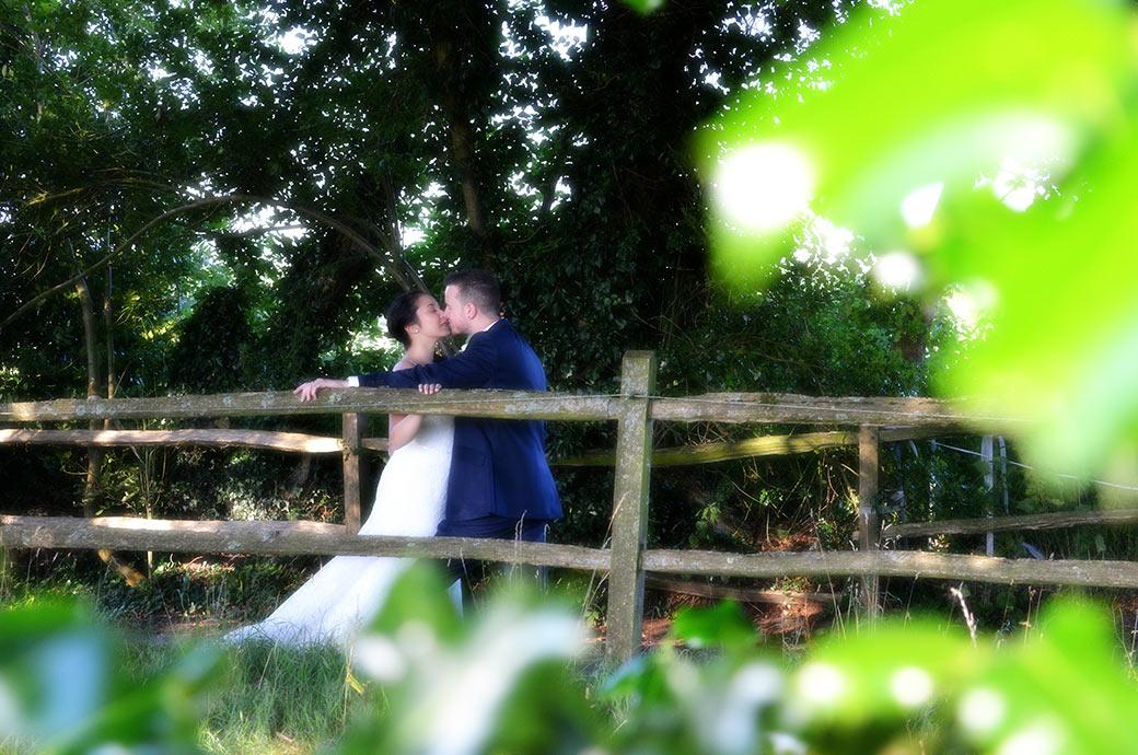 Discrete wedding picture taken through the trees in a field of the bride and groom leaning on a fence in the lane having a kiss at the rural Clock Barn Hall by the Surrey Downs