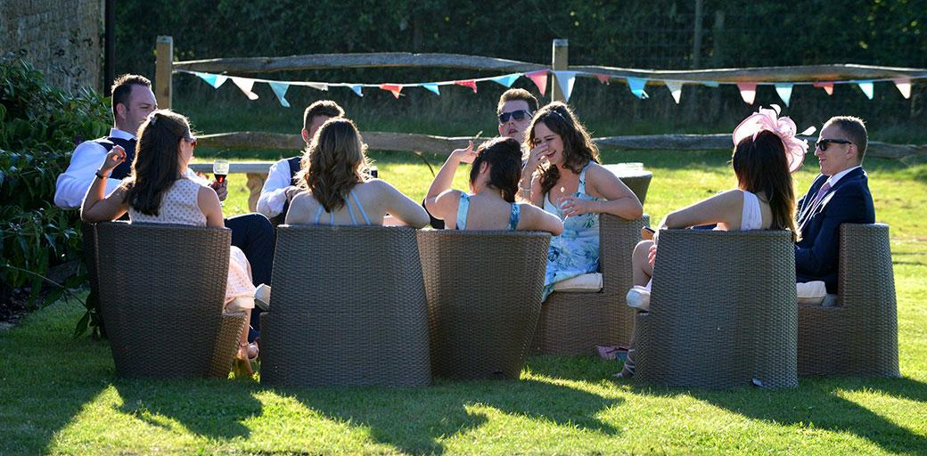 Wedding guests relax in the rattan chairs  on the lawn over drinks as they enjoy a chat in the sun at the peaceful Barn Hall Godalming wedding venue located in the Surrey countryside