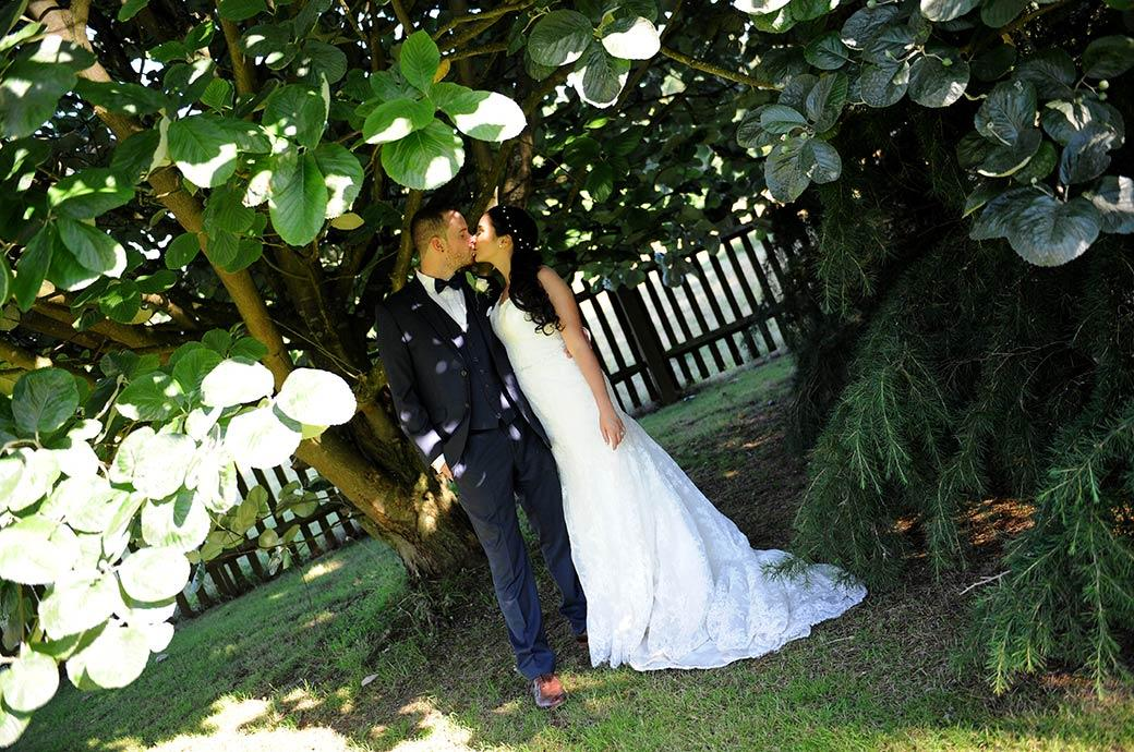 Beautiful wedding picture of a newlywed couple romantically kissing under a tree at the delightful rural and informal wedding Surrey wedding venue Clock Barn Hall in Godalming