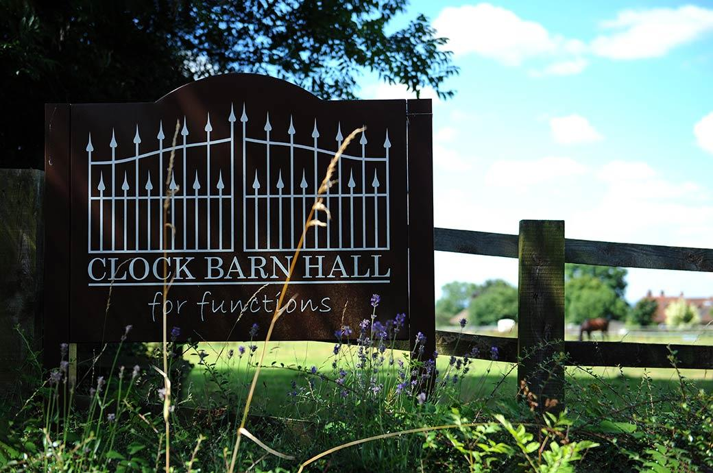 Wooden signpost to the relaxed, informal and rural Surrey wedding venue Clock Barn Hall Godalming situated on a working farm in beautiful countryside