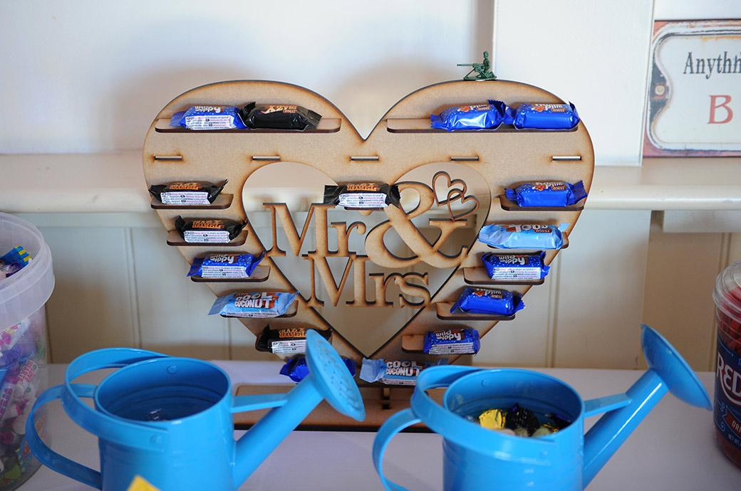 Blue watering cans and chocolate bars on a heart shaped shelf captured in this wedding photo by a Surrey Lane wedding photographer at the Clock Barn Hall in Godalming