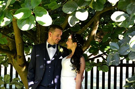 Handsome young newlywed couple standing romantically under a tree at the beautiful and relaxing Clock Barn Farm a delightful wedding venue in Godalming Surrey