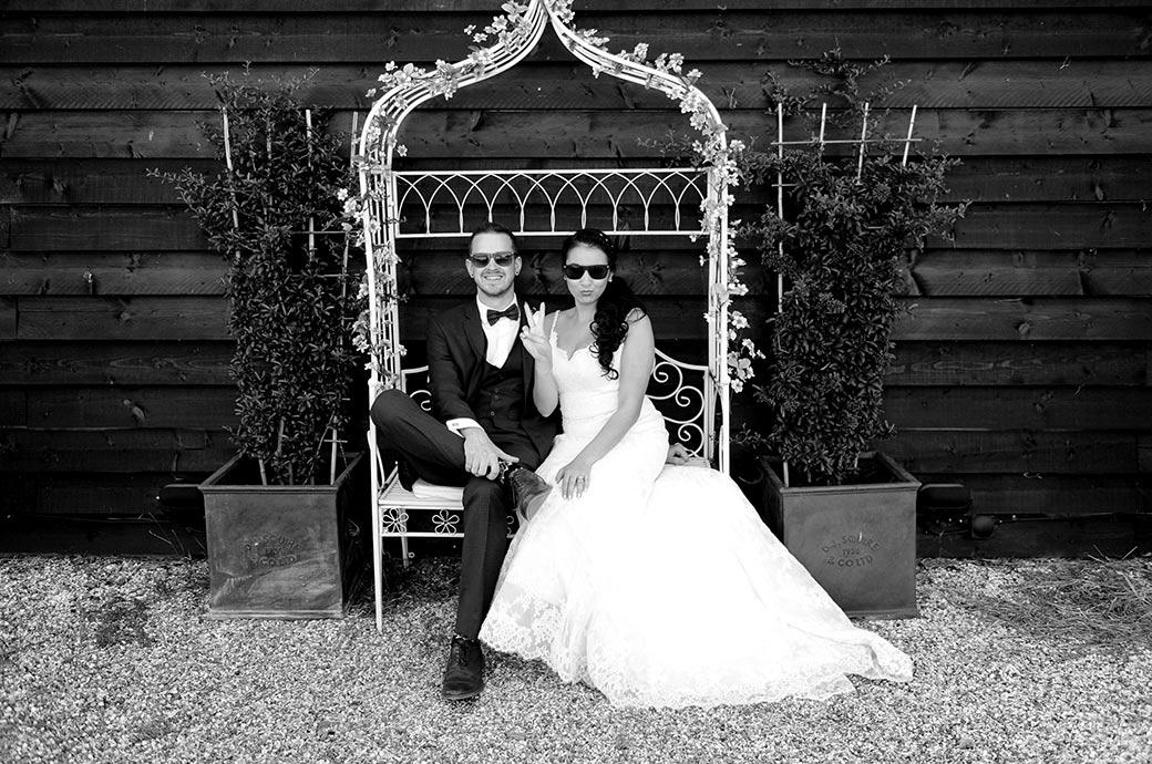 Bride with Smiling Groom sitting in an ornamental iron chair wearing sunglasses at the lovely rural Surrey wedding venue Clock Barn Hall in Godalming showing a victory  peace sign