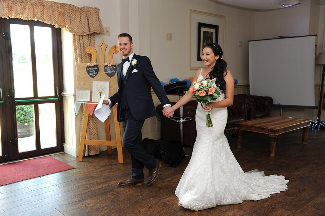 An excited and very happy Bride and Groom enter the reception hall for the start of the wedding breakfast at the relaxed and rural Surrey wedding venue Clock Barn Hall Godalming