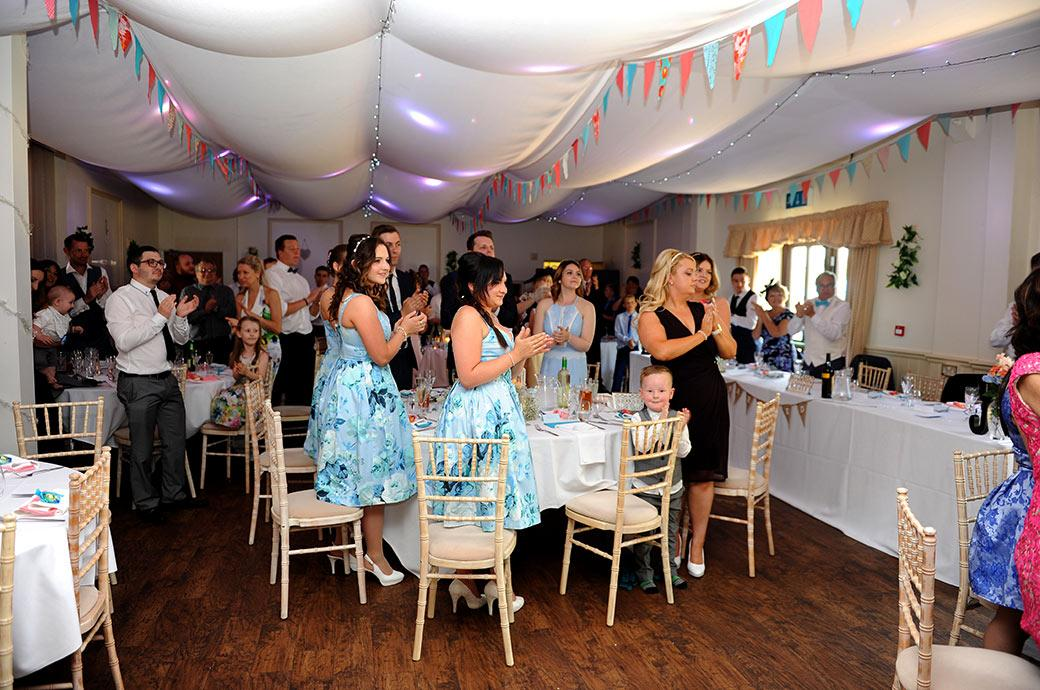 Wedding guests standing up and clapping at the entrance of the Bride and groom at rural Surrey wedding venue Clock Barn Hall for the commencement of the wedding breakfast