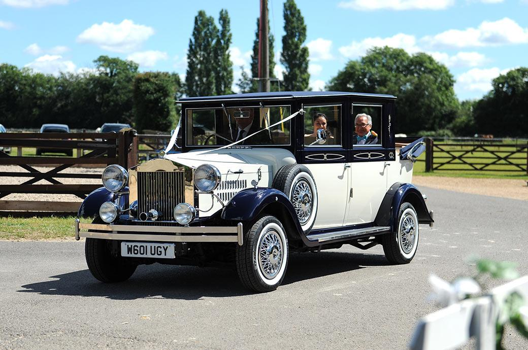 The arrival at  Surrey wedding venue Clock Barn Hall Godalming of the Bride and her father in their classic Regent Landaulette wedding car