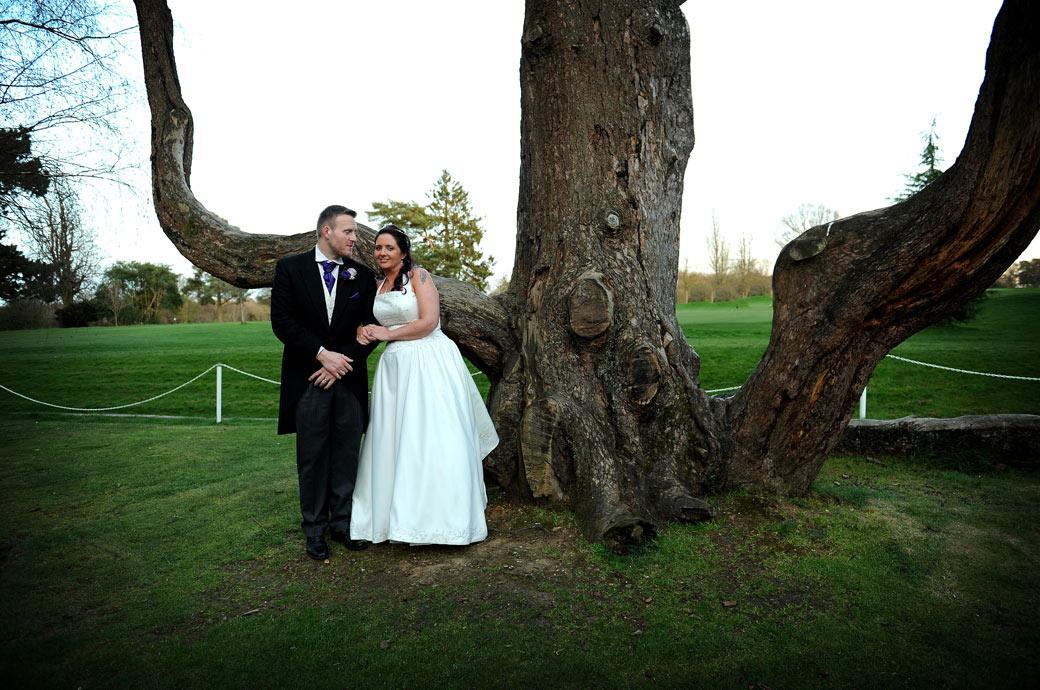 Newlywed couple taking a break from the evening celebrations captured in this wedding photograph standing by an ancient and unusual looking tree at Coulsdon Manor Surrey
