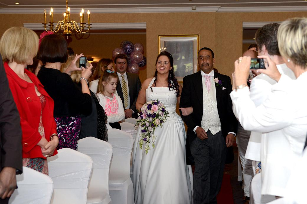 A delighted and radiant Bride smiles as she walks down the aisle of The Blenheim Suite on her father's arm in this Coulsdon Manor Surrey wedding photo