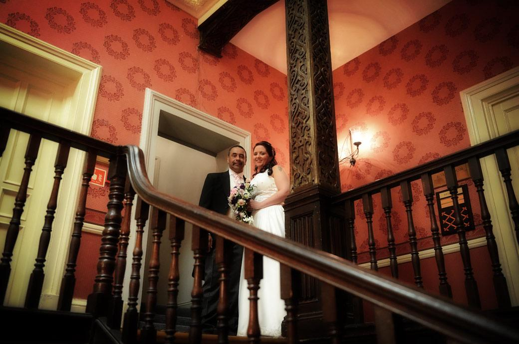 Bride standing with her father at the top of the ornate wooden staircase in this wedding photograph take at Coulsdon Manor a Surrey wedding venue with a long history