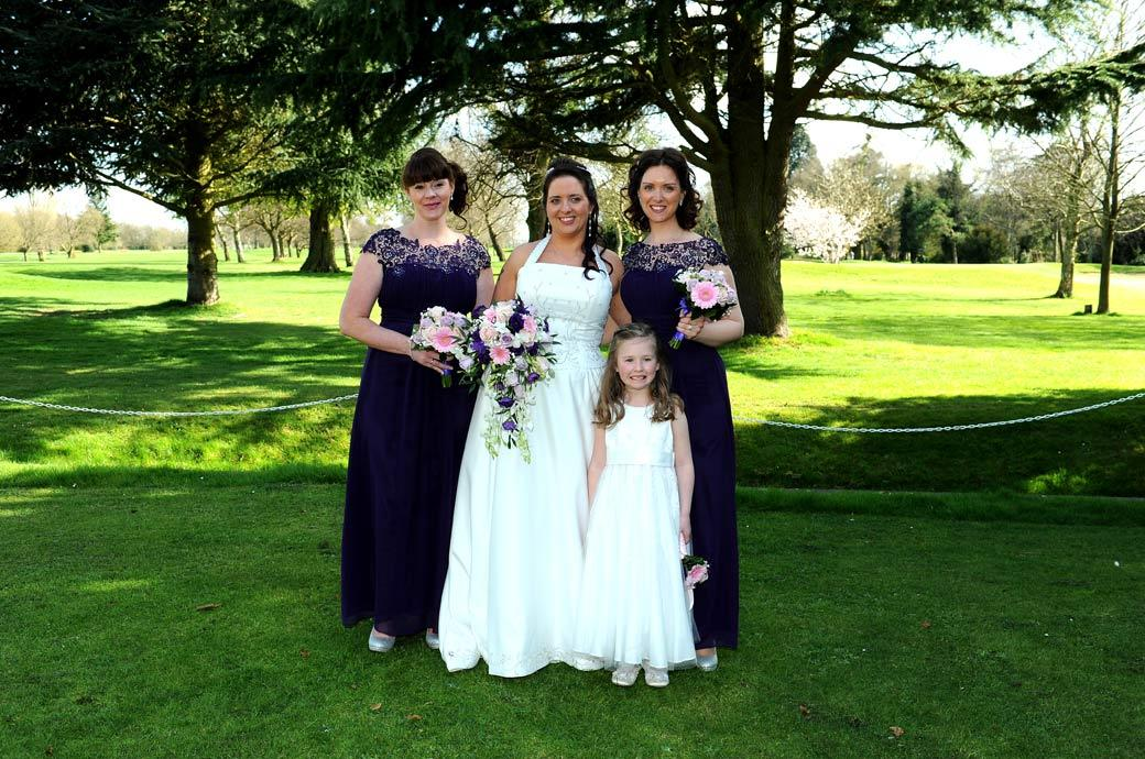A Surrey Bride with her Bridesmaids and flower girl in this lovely relaxed wedding picture taken at Coulsdon Manor with its beautiful green backdrop