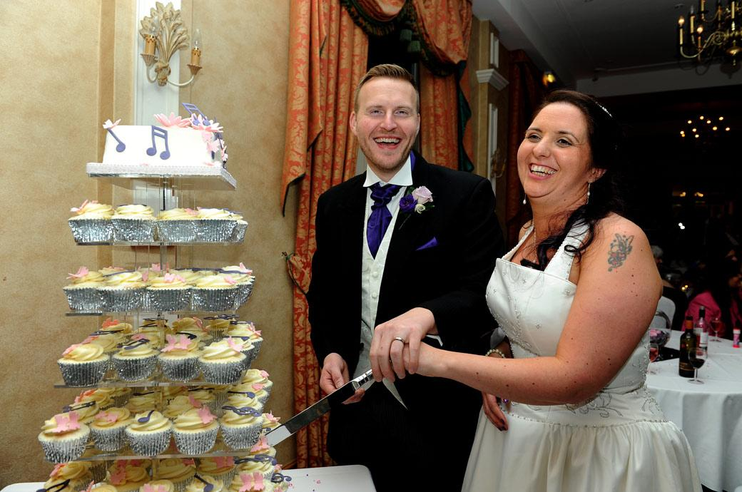 Wedding photograph of a happy laughing Bride and Groom as they prepare to cut their wedding cake in The Manor House Suite at Coulsdon Manor Surrey