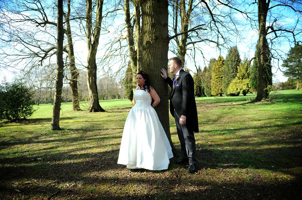 Bride and groom standing in the trees near the fairway enjoying the views and tranquility in this relaxed natural wedding picture from Surrey wedding venue Coulsdon Manor