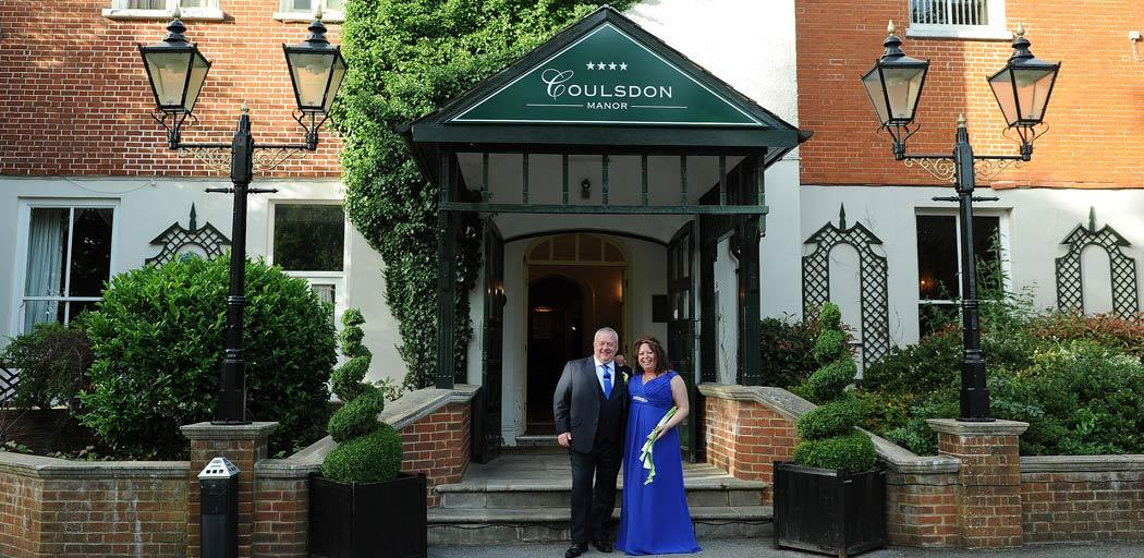 Wedding picture of a smiling Bride and groom standing at the front of Coulsdon Manor a Surrey wedding venue built in 1850 and reatining many original features
