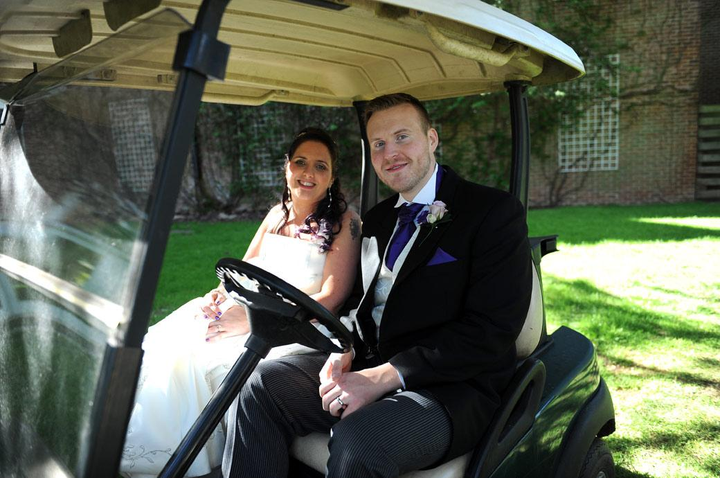 A smiling newlywed couple relaxing in a golf buggy ready to go off for some romantic wedding photos in the lovely grounds of Surrey wedding venue Coulsdon Manor