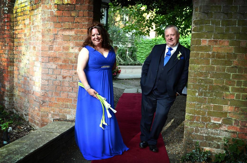 A relaxed Bride and groom strike a nonchalant pose in this wedding photograph taken as they stand on the red carpet in the archway to the Coulsdon Manor terrace