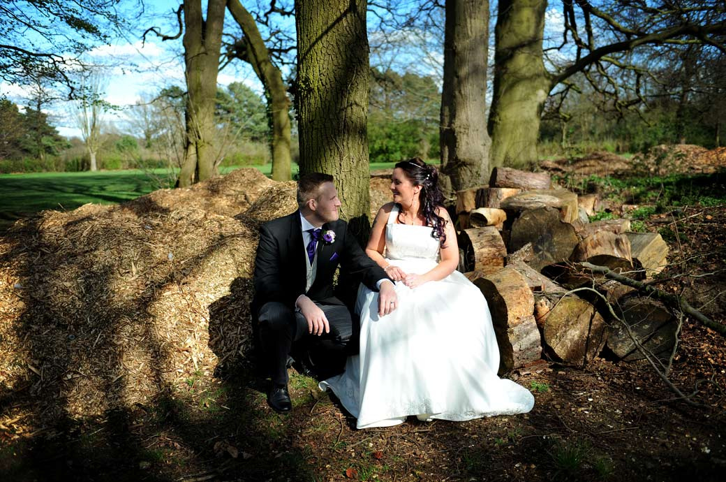 Loving newlyweds enjoying a tranquil moment together by a woodpile in the forest captured in this relaxed wedding photograph taken at Surrey wedding venue Coulsdon Manor