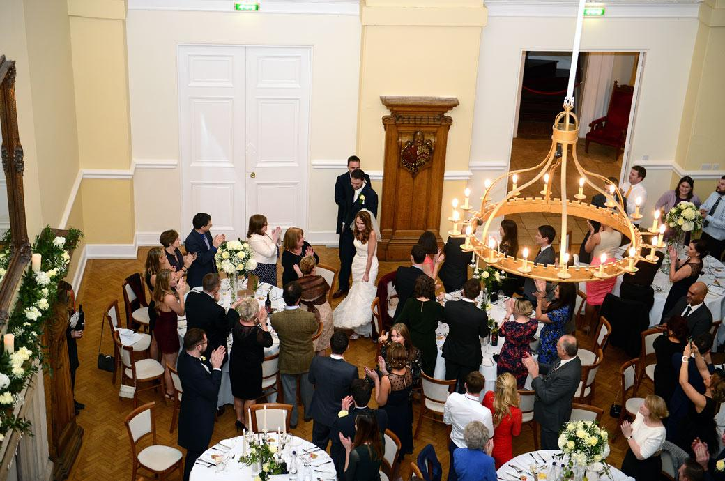 Aerial wedding photo taken from the balcony of the married couple walking into The Great Hall at Farnham Castle in Surrey for the Wedding Breakfast as family and guests applaud